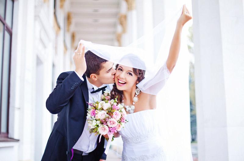 Brautpaar unterm Schleier mit einem Brautstrauß in der Hand